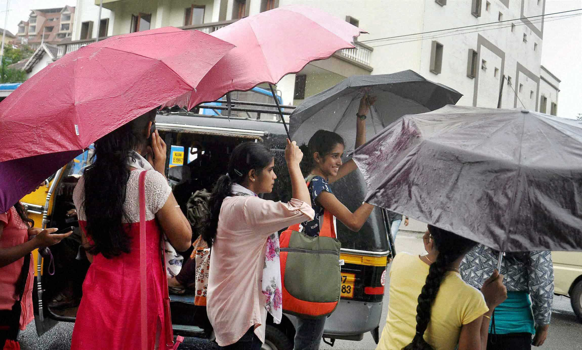 Girls enjoying premonsoon drizzle in Kochi. PTI
