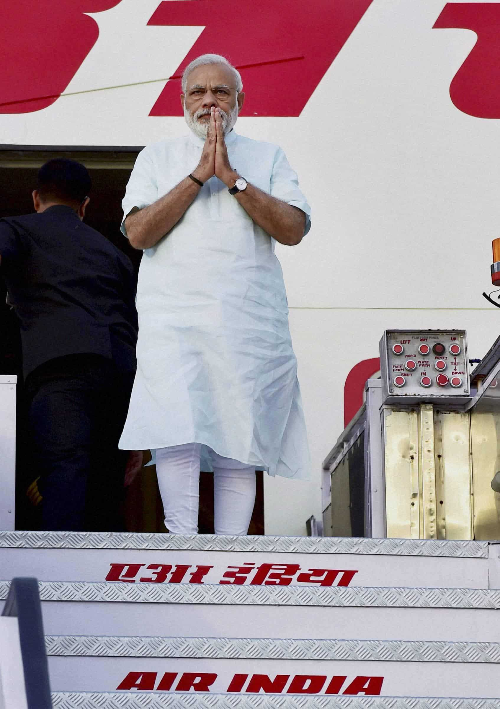 Prime Minister Narendra Modi gestures as he alights the stairs of the plane after returning from his five-nation tour at Air Force Station. PTI