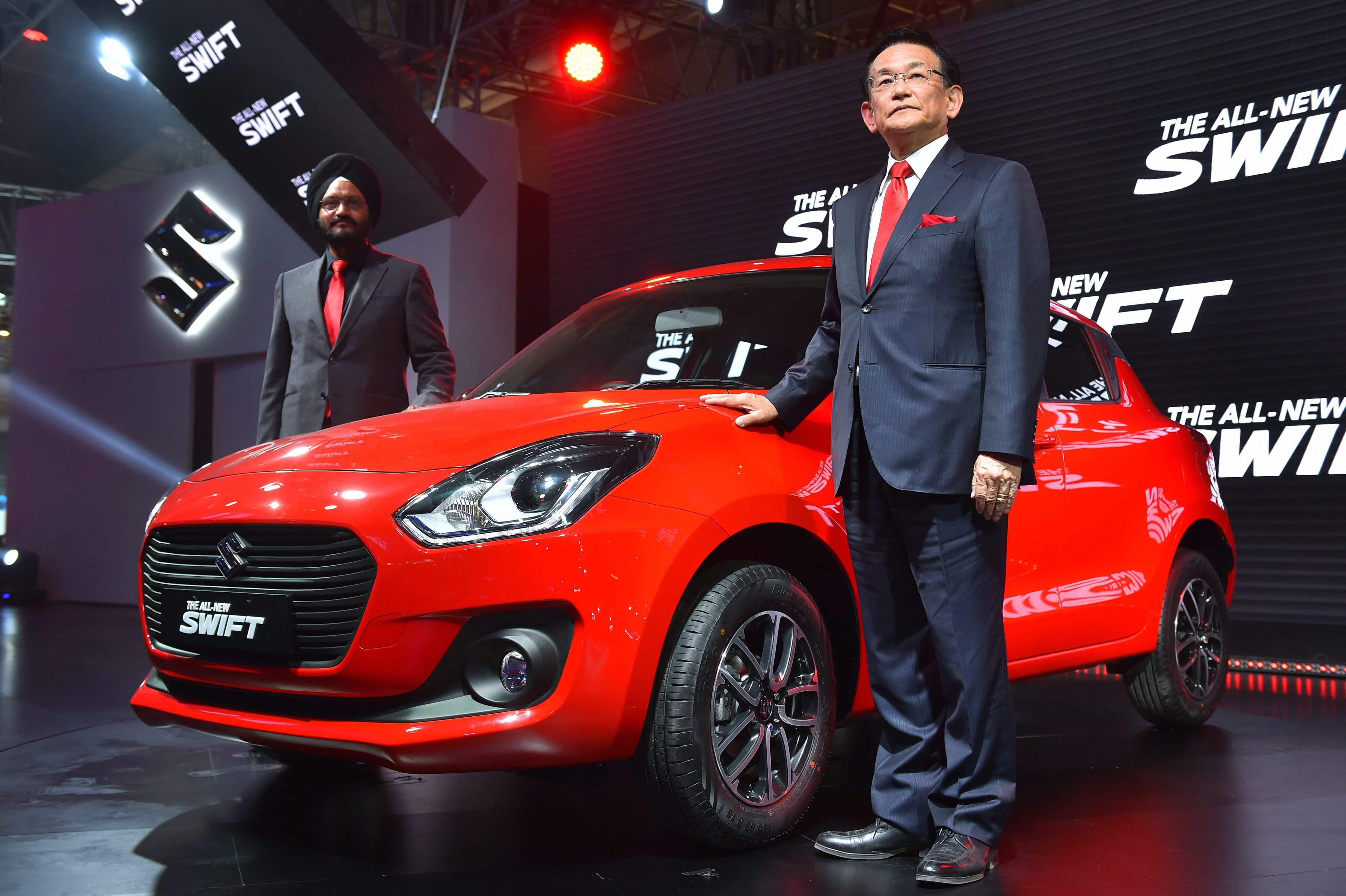 Maruti Suzuki's Managing Director & CEO Kenichi Ayukawa (R) and Senior Executive Director, Marketing and Sales, RS Kalsi showcase the company''s all-new Swift at the Auto Expo 2018 in Greater Noida.  PTI