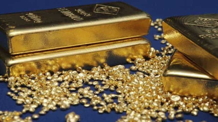 Gold prices inch down as dollar firms