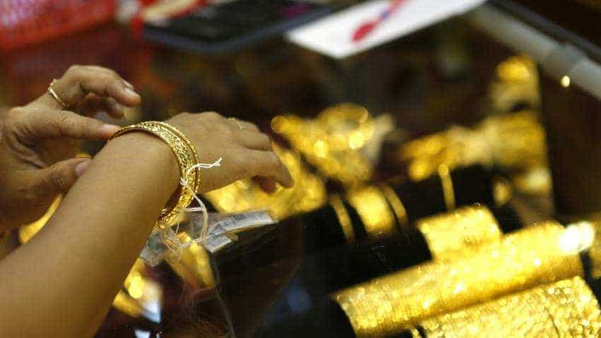 Gold edges down as Federal Reserve interest rate view strengthens dollar