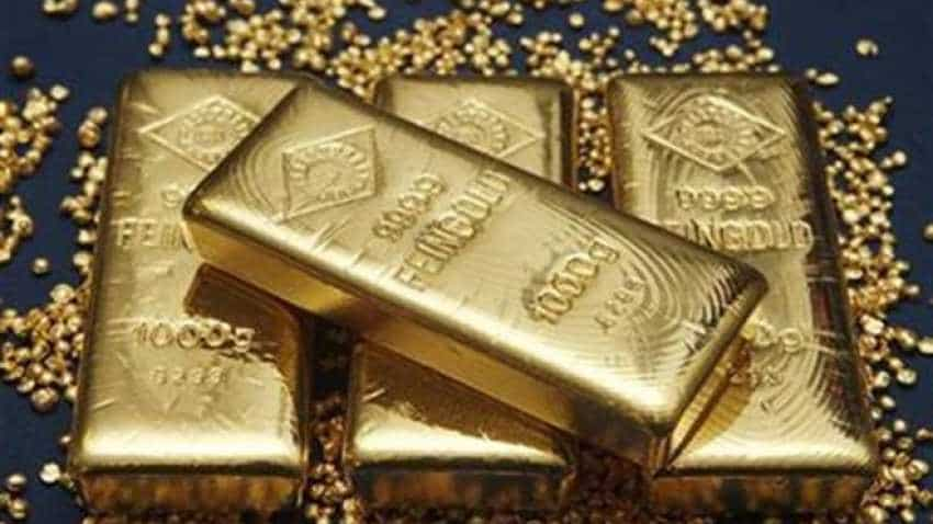 Gold inches down as trade worries boost dollar
