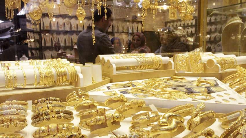 Gold eases below $1,800 as dollar firms, virus fears limit losses